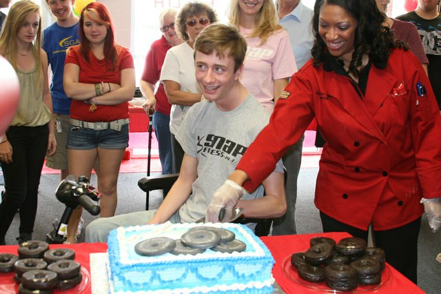 Jordan Murphy cuts the cake during a day in his honor at SNAP Fitness in Oviedo March 24. 