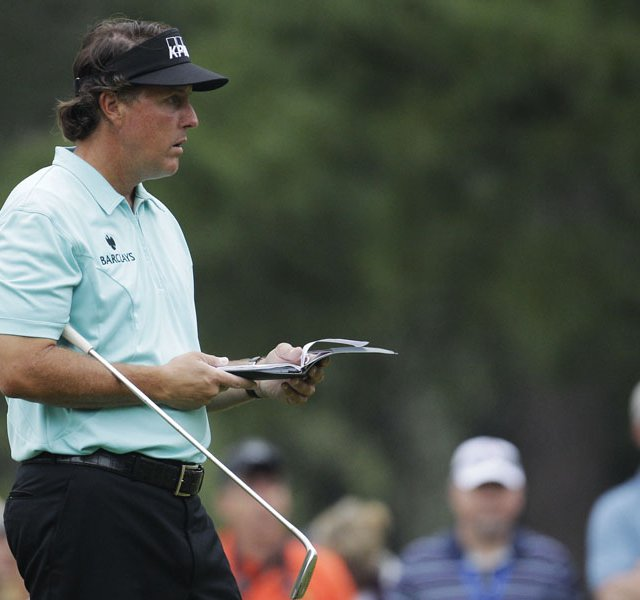 Phil Mickelson checks his notebook on the first green during a practice round for the Masters.