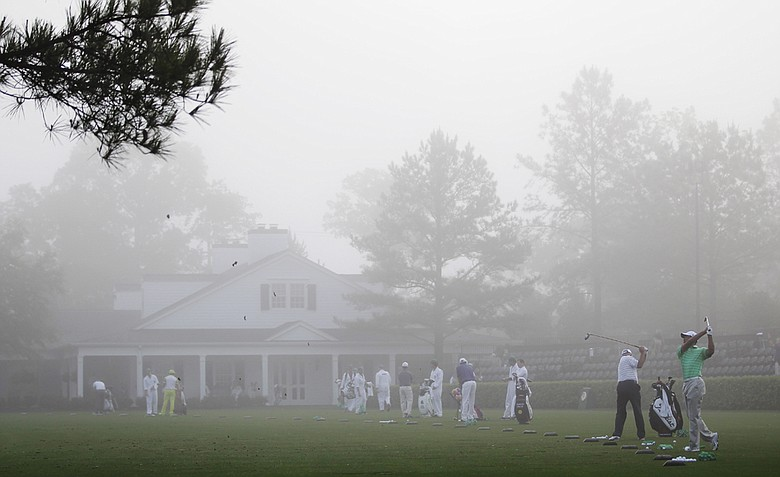 Tiger Woods hits balls during a Wednesday morning fog at Augusta National.