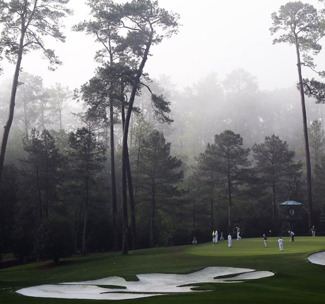 Players putt on the 10th green in the morning fog during a practice round for the Masters.