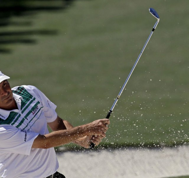 Fred Couples hits out of a bunker on the second hole during the third round of the Masters.