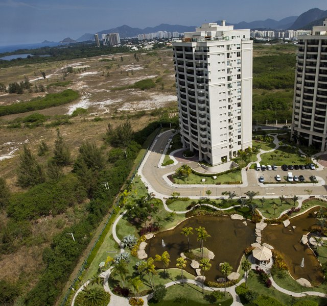 Luxury condominiums overlook the area, on left, where the Rio 2016 Olympic golf course is planned to be built in Rio de Janeiro&#39;s Barra da Tijuca neighborhood, Brazil. Rio 2016 organizers faced an unexpected challenge to deliver the first Olympic golf tournament in more than 100 years because of a legal dispute over the land where the historic course is supposed to be built.