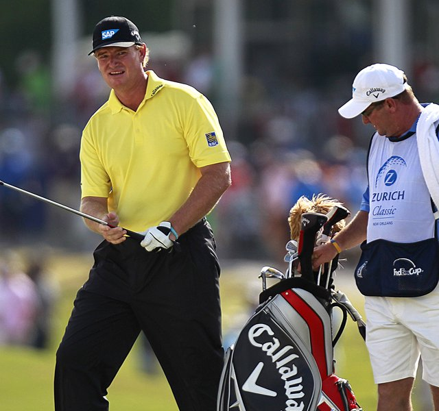 Ernie Els hits a shot during the Zurich Classic with caddie Ricci Roberts by his side.