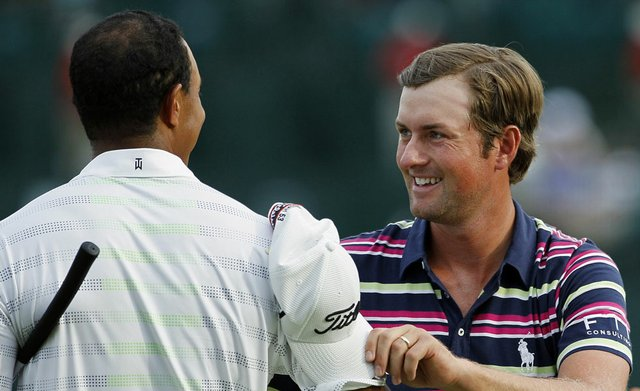 Webb Simpson, right, shakes hand with Tiger Woods on the 18th green following their first round of the Wells Fargo Championship.