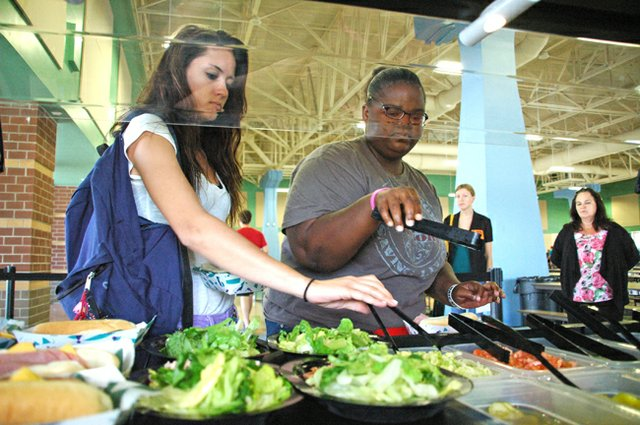 Oviedo High School students Cassandra Vivian and JoQwanda Sykes pick salads at the new donated salad bar from Duda Farm Fresh Foods.