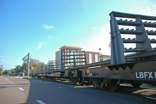 Rail cars carry new rails through Maitland to stops where the SunRail system will add additional tracks.