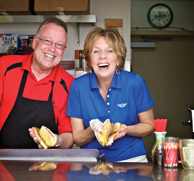 Steve Parrish (left) and Candy Parrish-Thrush serve up their famous burger dogs in much the same fashion as their father did 60 years ago.