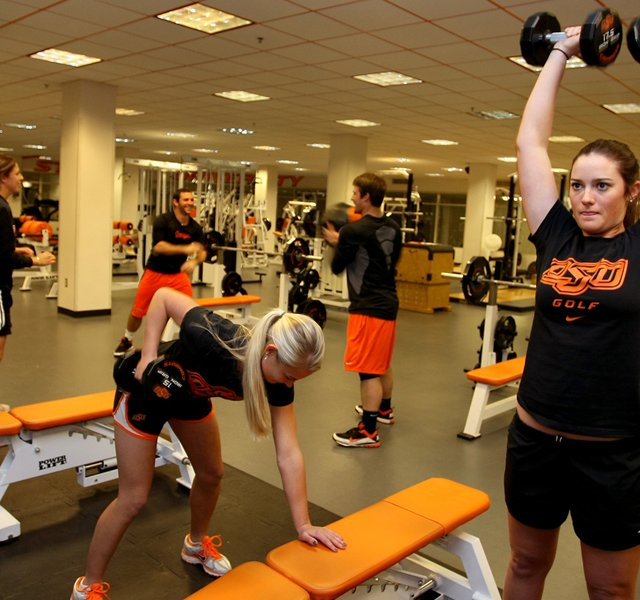 Oklahoma State players Kelsey Vines (right) and Josephine Janson work out while sharing the gym with members of OSU's baseball team.