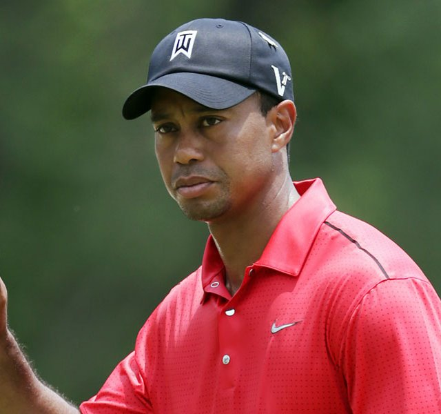 Tiger Woods acknowledges the gallery after making par on the first green during the final round of the AT&amp;T National.