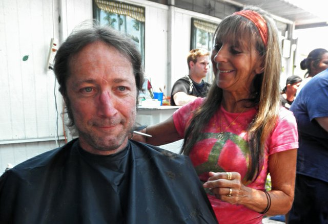 Luisa Perez cuts Dean Moscato's hair at The Vine Thrift Store's free lunch event where they also offer free haircuts.