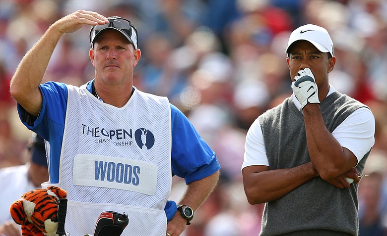 Tiger Woods looks on alongside caddie Joe LaCava before hitting his tee shot on the fifth hole during the third round of the 141st Open Championship at Royal Lytham & St. Annes Golf Club.