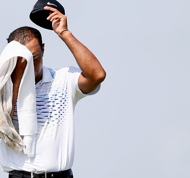 Tiger Woods wipes his head while on the fourth hole during the third round of the 94th PGA Championship. Woods would bogey the hole after hitting a fan with his tee ball and his approach shot.