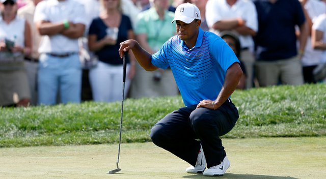 Tiger Woods gingerly bends down to line up a putt on the ninth green during the second round of The Barclays at the Black Course at Bethpage State Park August 24, 2012.