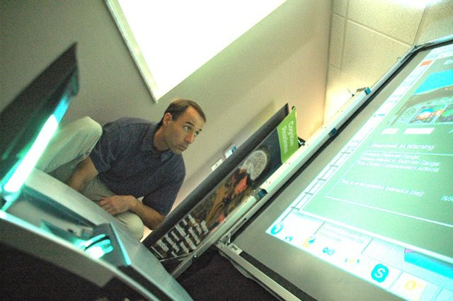 Design Interactive VP Matt Archer sets up a flight simulator inside the company's Oviedo headquarters. Oviedo and Winter Springs are using new incentives to lure businesses to keep residents in town.