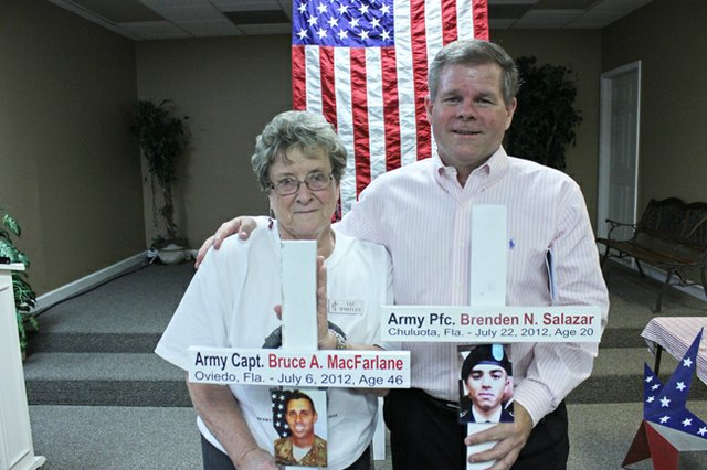 Liz Whitley and Jim Vanderbleek stand with memorials Vanderbleek made to honor fallen soldiers. Whitley works to support military families and to send care packages to soldiers away from home.