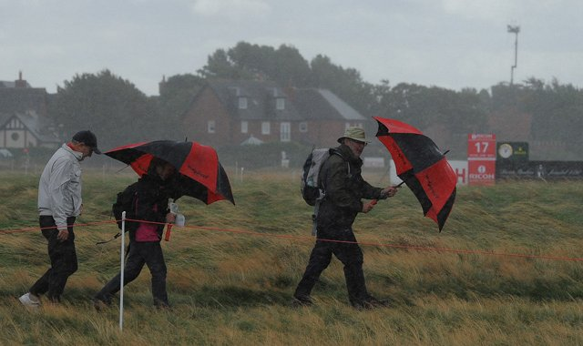 Spectators wait in bad weather for play to resume during the second round of the Women's British Open at the Royal Liverpool Golf Club in Hoylake, northern England.