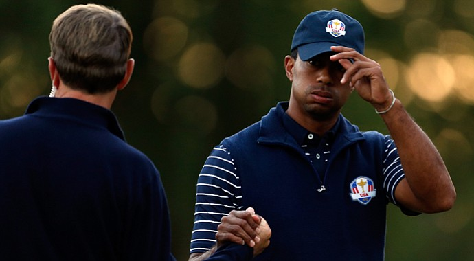 USA team captain Davis Love III greets Tiger Woods on the 18th green after Woods' afternoon four-ball loss Saturday at the Ryder Cup at Medinah Country Club.