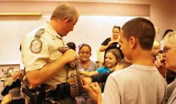 State Police Officer Steve McDaniel shows a 9-foot boa constrictor to students at Stenstrom Elementary's STEM night on Sept. 25.