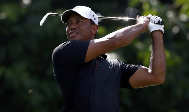 Tiger Woods watches his tee shot on the 2nd hole during the second round of the CIMB Classic.