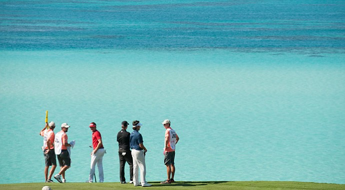 Keegan Bradley, Webb Simpson, and Bubba Watson look out at the ocean on the ninth hole during the final round of play at The Port Royal Golf Club for the 30th Grand Slam of Golf.