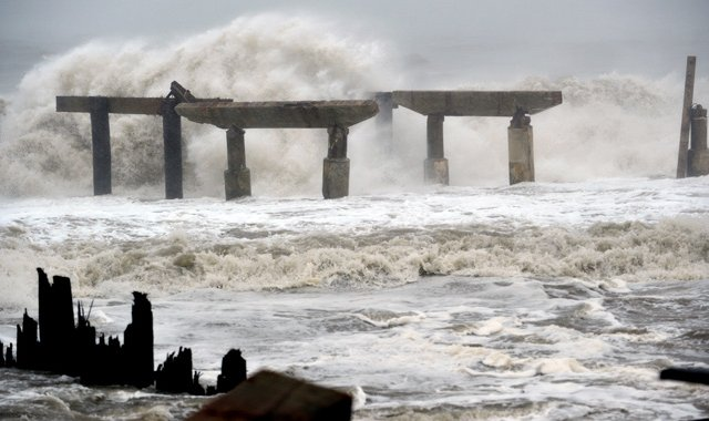 Waves crash against a previously damaged pier before landfall of Hurricane Sandy October 29, 2012 in Atlantic City, New Jersey. Storm-driven waves crashed ashore and flooded seafront communities across a swathe of the eastern United States as Hurricane Sandy barreled towards land.