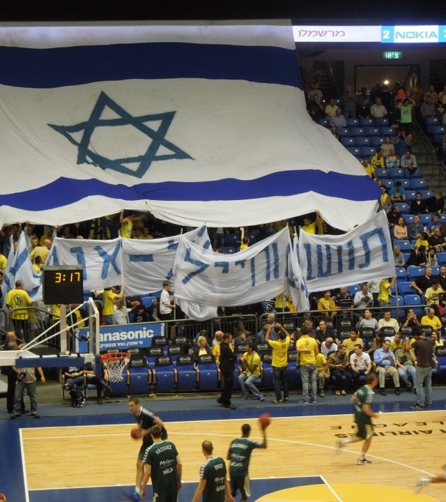 Fans attending the Maccabi Tel Aviv basketball game on Thursday night unfurl an oversized Israeli flag and sign in Hebrew that says , &quot;People of the South and soldiers, we are with you.&quot;
