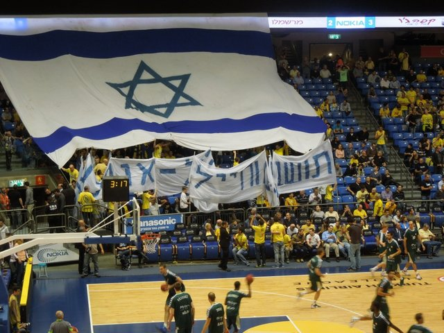 "Fans attending the Maccabi Tel Aviv basketball game on Thursday night unfurl an oversized Israeli flag and sign in Hebrew that says , ""People of the South and soldiers, we are with you."""