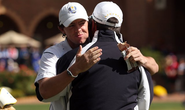 Rory McIlroy of Europe hugs his captain Jose Maria Olazabal on the putting green after arriving late to the golf course during the singles matches for The 39th Ryder Cup at Medinah Country Club.