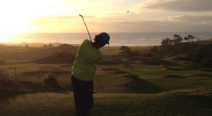 Bradley S. Klein hits a tee ball at dusk at Bandon Preserve in Oregon.
