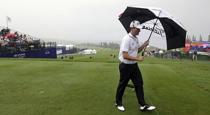 Webb Simpson walks under an umbrella on the first tee as he waits to start the first round at the Tournament of Champions golf tournament Friday, Jan. 4, 2013, in Kapalua, Hawaii. After a morning of severe wind and rain, tournament officials suspended play and scratched the day.