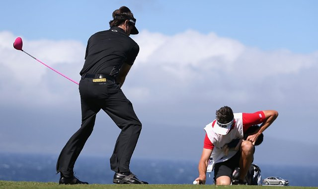 Bubba Watson pretends to tee off as his caddie Ted Scott holds a finger on the ball to keep it from blowing away on the 10th hole during the replay of the first round of the Hyundai Tournament of Champions.