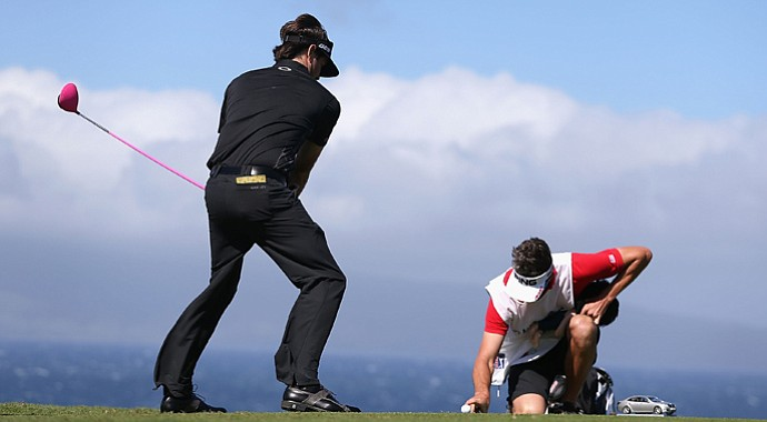 Bubba Watson pretends to tee off as his caddie Ted Scott holds a finger on the ball to keep it from blowing away on the 10th hole during the replay of the first round of the Hyundai Tournament of Champions. The tournament didn't end until Tuesday.