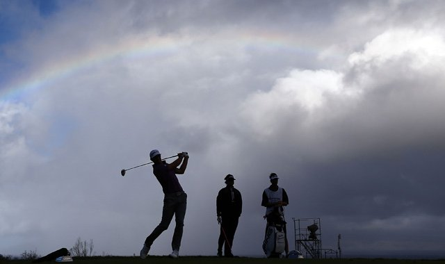 Dustin Johnson hits a tee shot under a partial rainbow on the 13th hole during the replay of the first round of the Hyundai Tournament of Champions at the Plantation Course.