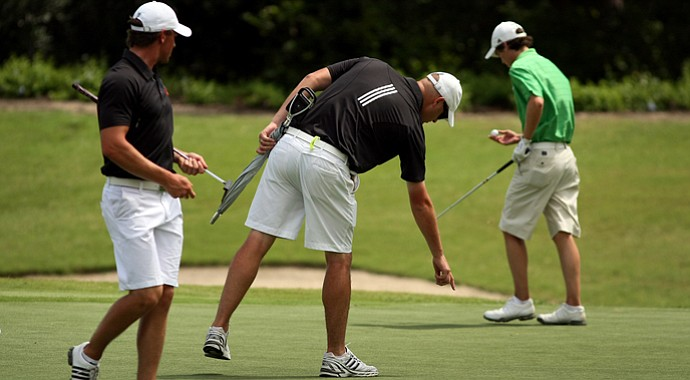 Louisville's assistant coach Andrew Tredway points out the line for his player Max Walz at No. 8 during the final round of the Big East Men's Championship. Louisville was the runner-up to Notre Dame.
