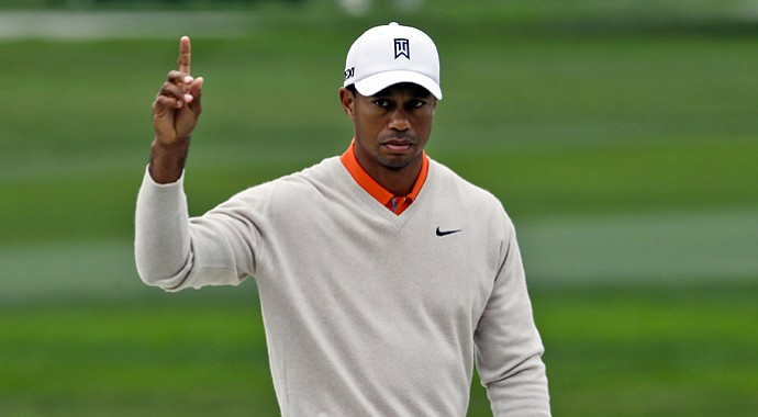 Tiger Woods gestures after his shot out of a bunker on the par-5 sixth hole on the South Course at Torrey Pines goes into the cup for an eagle during the first round of the Farmers Insurance Open golf tournament Thursday Jan. 24, 2013, in San Diego.