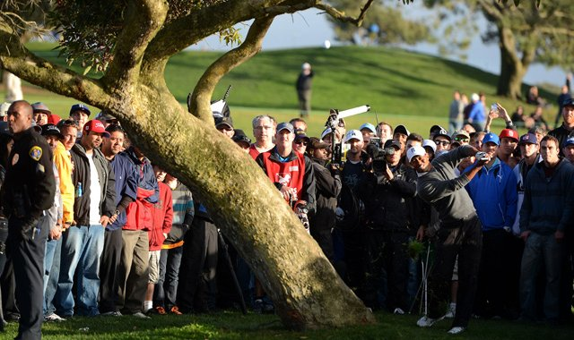 Tiger Woods hits out of the rough on the 4th hole during the final round at the Farmers Insurance Open. He&#39;d chip in for a birdie on his next shot.