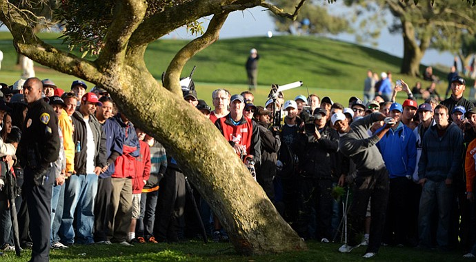 Tiger Woods hits out of the rough on the 4th hole during the final round at the Farmers Insurance Open. He'd chip in for a birdie on his next shot.