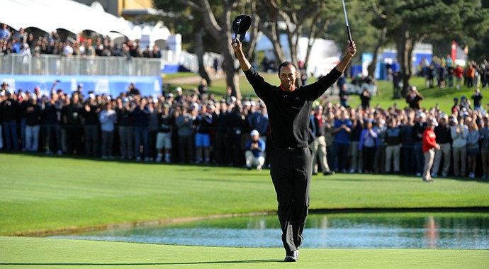 Tiger Woods celebrates on the 18th green after winning the Farmers Insurance Open.