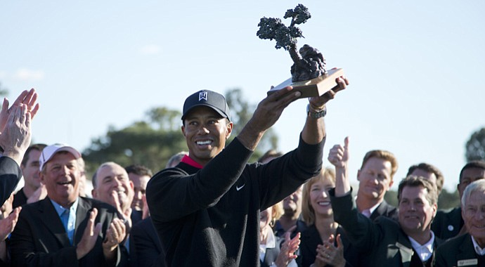 Tiger Woods raises his Farmers Insurance Open trophy at Torrey Pines.