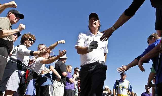 Phil Mickelson walks through a gauntlet of fans trying to give him a high-five as he walks to the third tee during the second round of the Waste Management Phoenix Open golf tournament Friday, Feb. 1, 2013, in Scottsdale, Ariz.