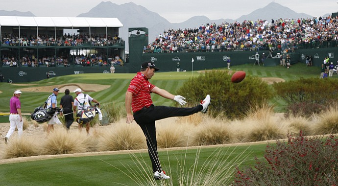 Padraig Harrington punts a football into the grandstands on the 16th hole during the final round of the Waste Management Phoenix Open.