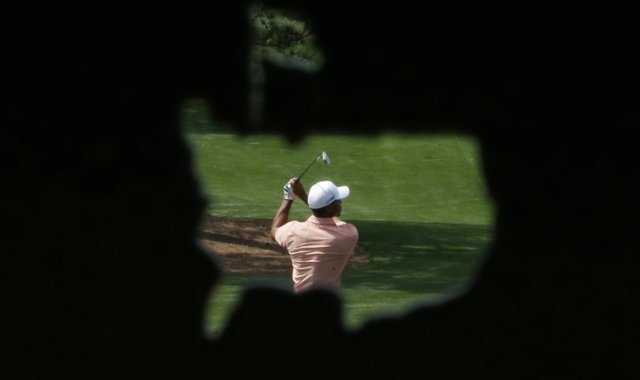 In a photo taken through a metal cutout of the Masters&#39; logo, Tiger Woods hits on the driving range during a practice round for the Masters.