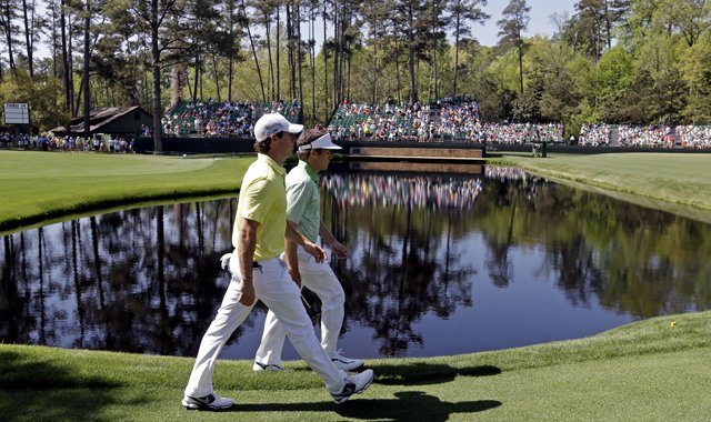 Rory McIlroy walks with amateur Michael Weaver to the 15th green during a practice round for the Masters.
