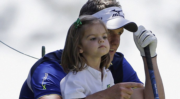 Luke Donald, of England, talks to his daughter during the Par-3 Contest at Augusta National.