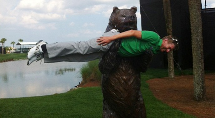 "David Lynn does a little ""planking"" in the arms of a bear."
