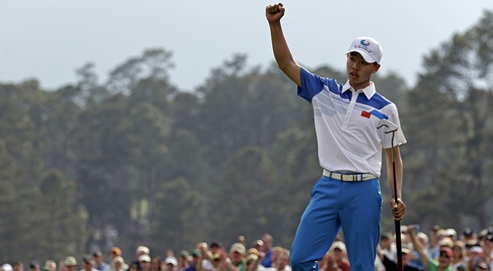 Amateur Guan Tianlang, of China, celebrates after a birdie putt on the 18th green during the first round of the Masters.