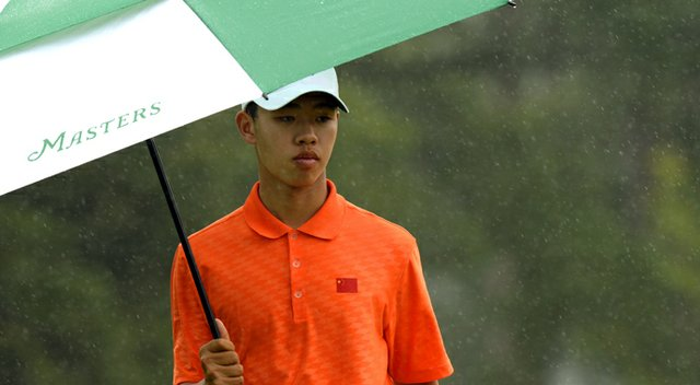Tianlang Guan plays in the rain during the second round of the 77th Masters.