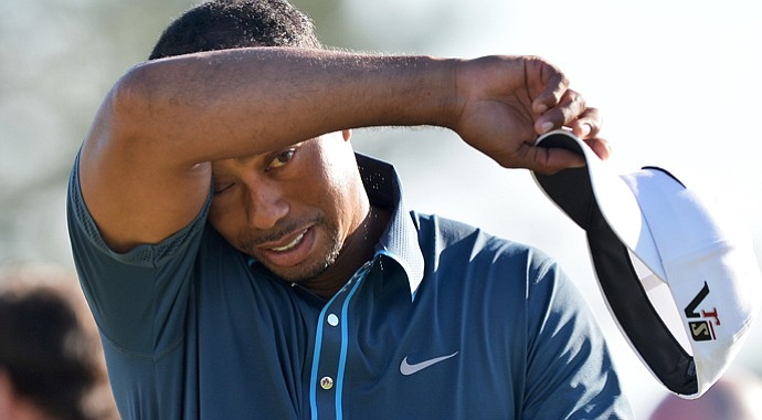 Tiger Woods wipes his brow after a par-save at 18 that helped him record a 2-under 70 and sit four shots off the lead.