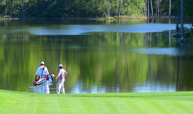 Greyson Sigg, right, and his caddie Bernard Dent feed the fishes off the 17th green during the junior-am on Thursday at the Junior Invitational.