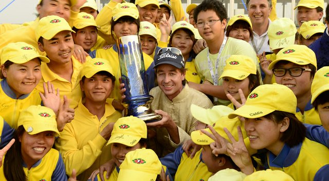 Brett Rumford, center, with the winner's trophy is surrounded by tournament volunteers after he won the China Open on Sunday.